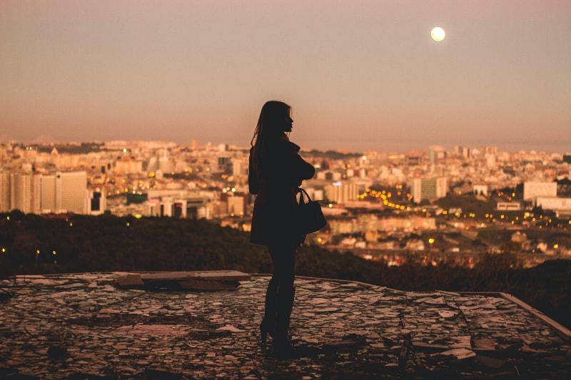 Schattenbild der Frau, die während der Fotografie der goldenen Stunde steht