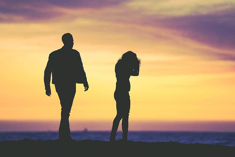 Silhouette eines Mannes und einer Frau bei Sonnenuntergang streiten
