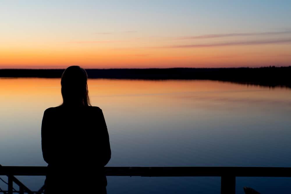 die Silhouette einer Frau, die bei Sonnenuntergang steht