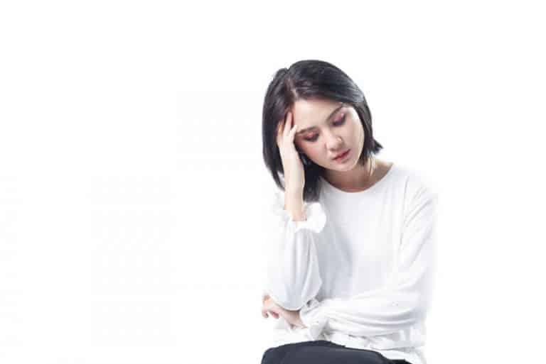ein Mädchen sitzt und bewacht ihren Kopf