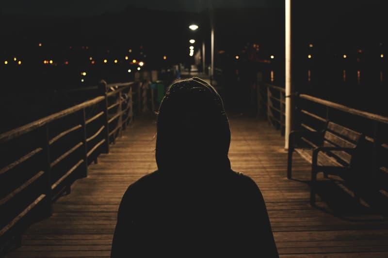 ein Mädchen mit Kapuze allein im Dunkeln