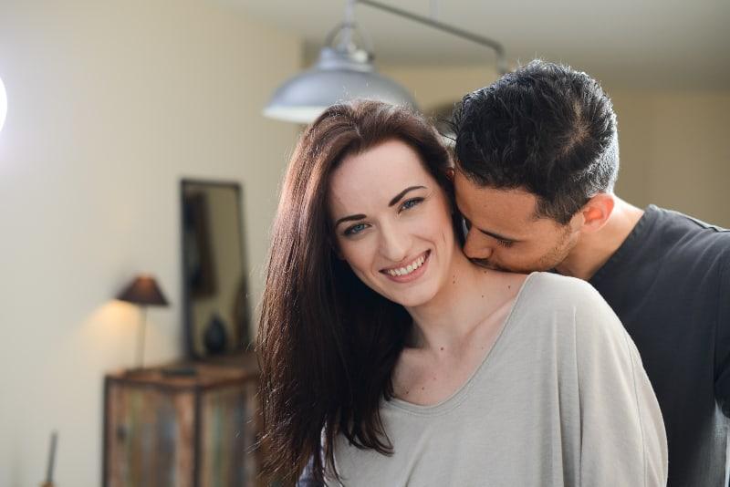 ein Mann, der ein Mädchen auf den Hals küsst