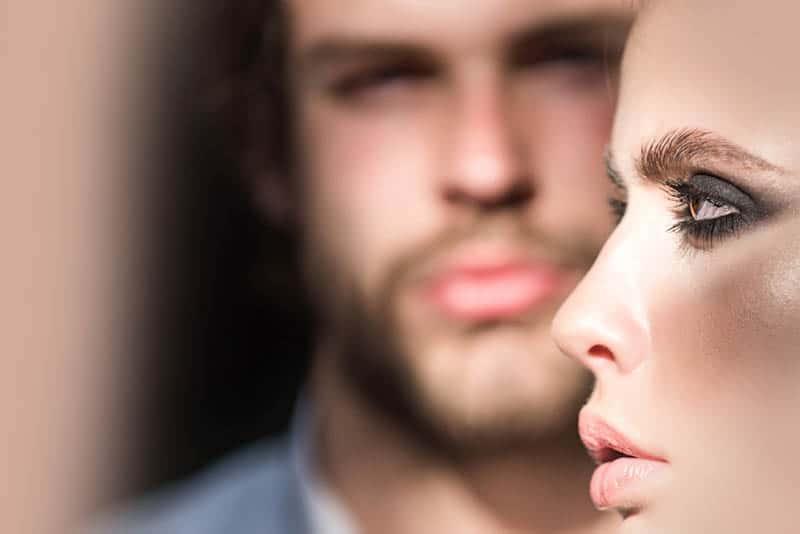 ein Mann mit Bart im Hintergrund des Gesichts einer Frau