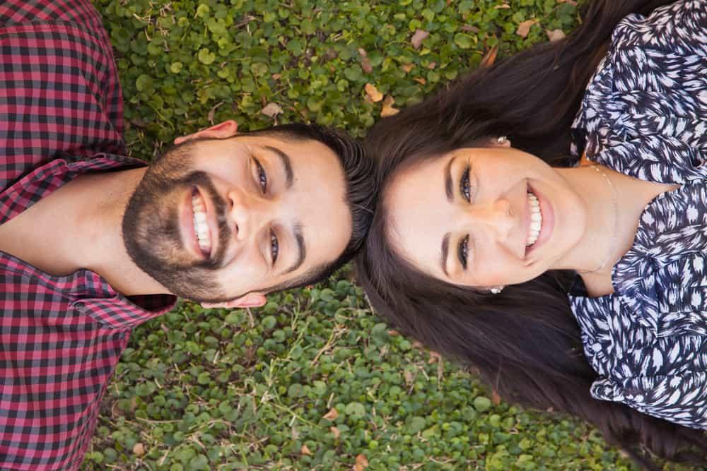 ein Mann mit Bart und eine Frau im Gras liegen