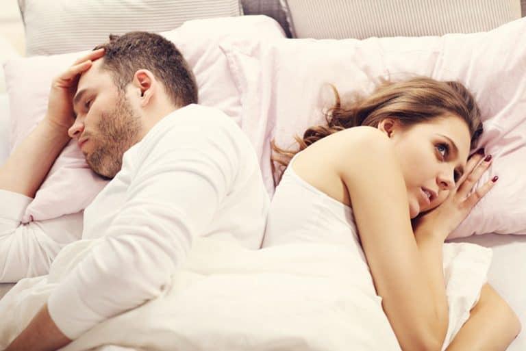 ein Paar im Bett liegend, den Rücken zueinander