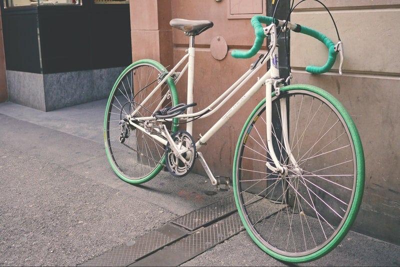 ein altes grünes Fahrrad an eine Wand gelehnt