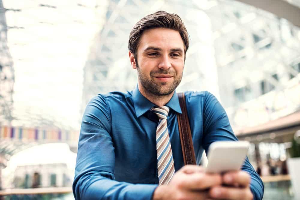ein junger lächelnder Geschäftsmann, der mit einem Handy in seinen Händen sitzt