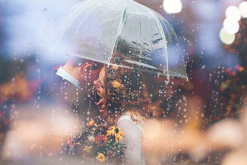 ein liebendes Paar, das im Regen unter einem durchsichtigen Regenschirm steht