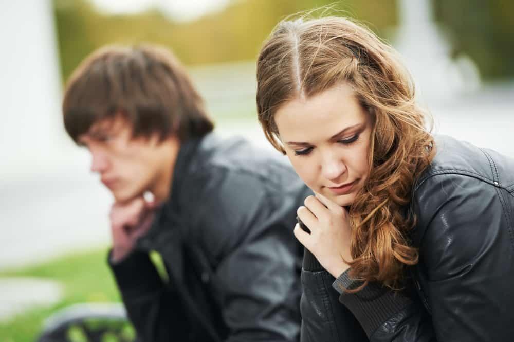 ein unglückliches Liebespaar, das auf einer Bank sitzt
