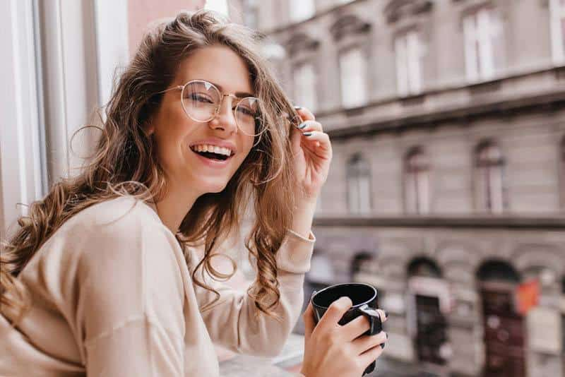 eine lächelnde Frau, die Kaffee am Gebäudefenster trinkt