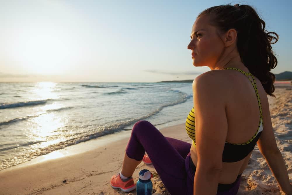 eine nachdenkliche Sportlerin, die am Strand sitzt