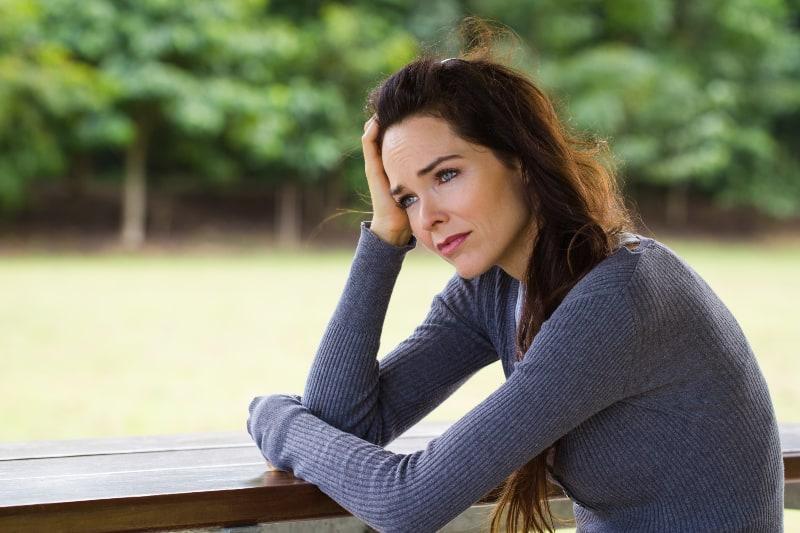 eine traurige und depressive Frau, die in der Natur sitzt