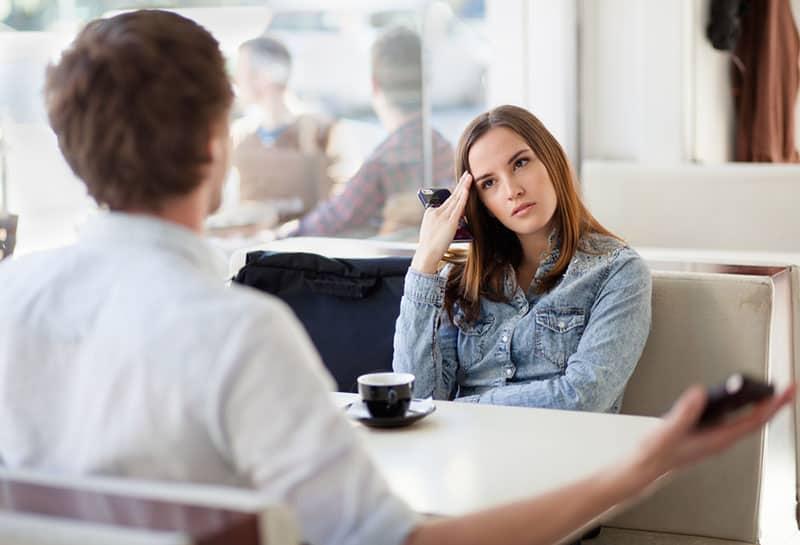 ernsthafte junge Frau, die Mann hört