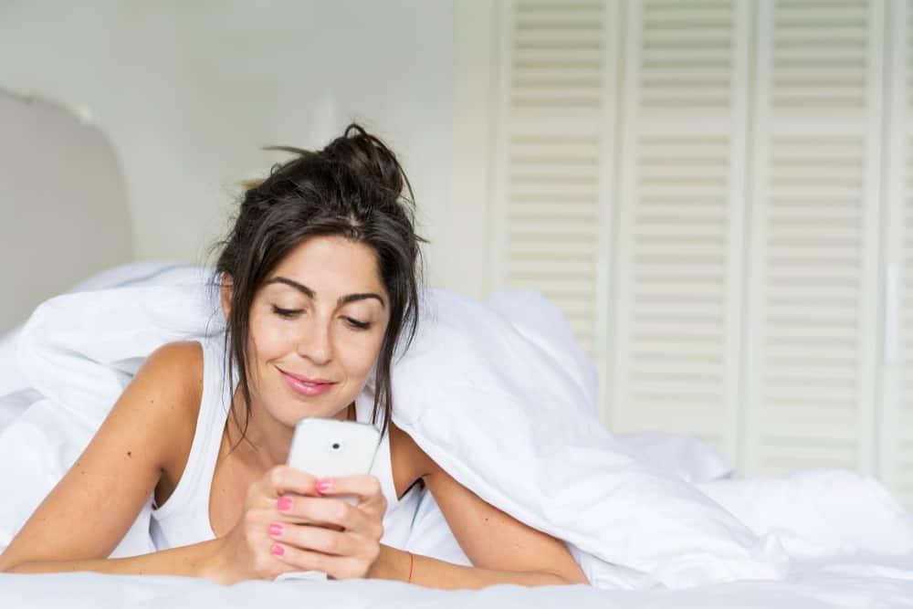 schöne Brünette, die auf dem Bett liegt und mit einem Lächeln auf ihr Handy schaut