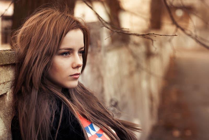traurige junge Frau, die draußen steht