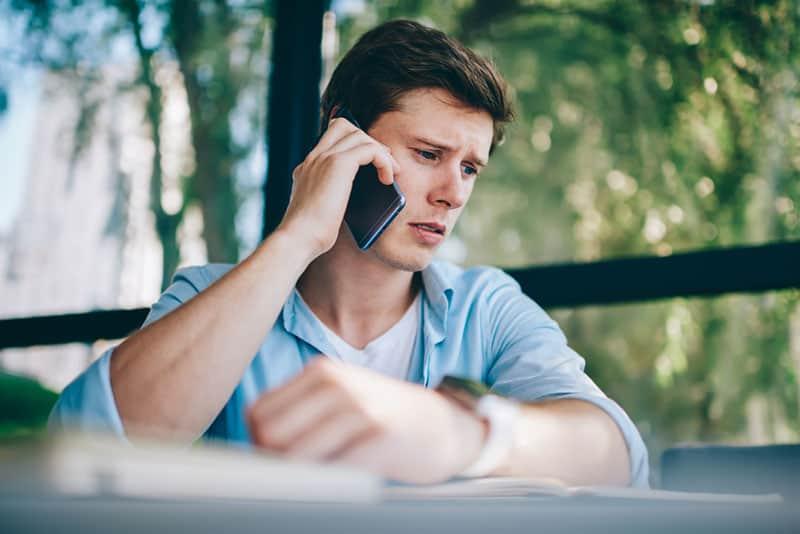 trauriger Mann, der am Telefon spricht