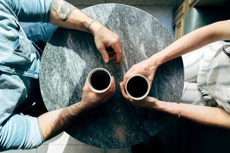 zwei Mann und Frau halten Tassen auf Tischen