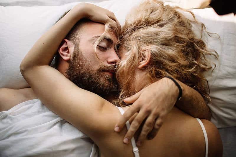 junges sexy Paar, das auf Bett kuschelt