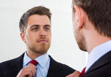 Porträt eines Geschäftsmannes, der sich im Spiegel betrachtet