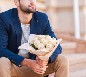 Mann in der intelligenten Jacke, die Blumenstrauß hält