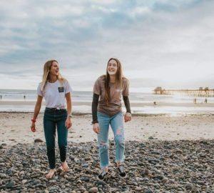 Zwei lächelnde Mädchen gehen zum Strand