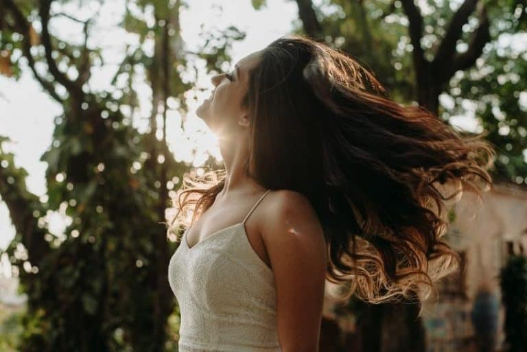 Das Mädchen in der Natur genießt die Sonne