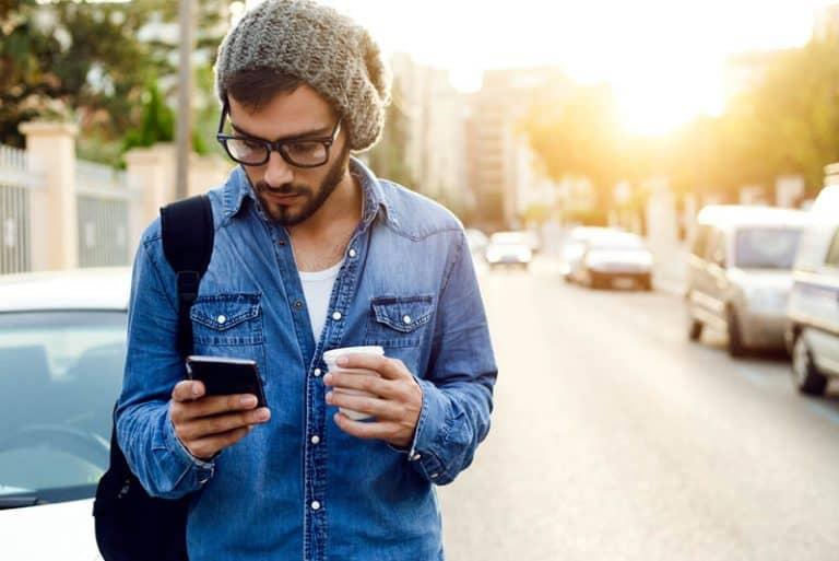 Ein Mann ging die Straße entlang und hielt ein Handy in den Händen