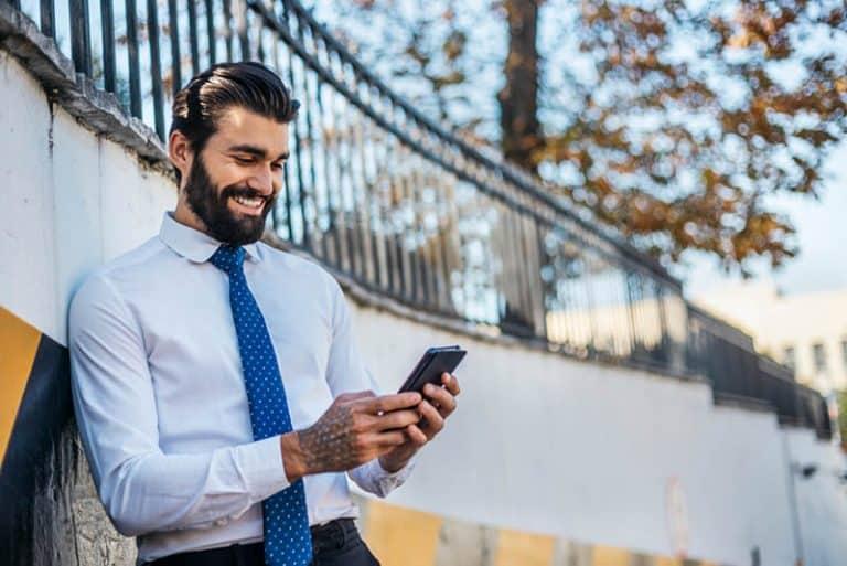Ein Mann im Anzug hält ein Handy in den Händen