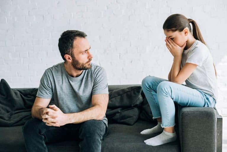 Ein Paar redete auf der Couch, ein überraschtes Mädchen bedeckte ihr Gesicht mit den Händen