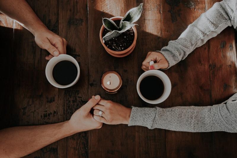 Ein Paar trinkt Kaffee und hält sich an den Händen