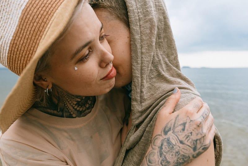 Ein trauriges Mädchen mit einem Tattoo umarmt ihre Freundin