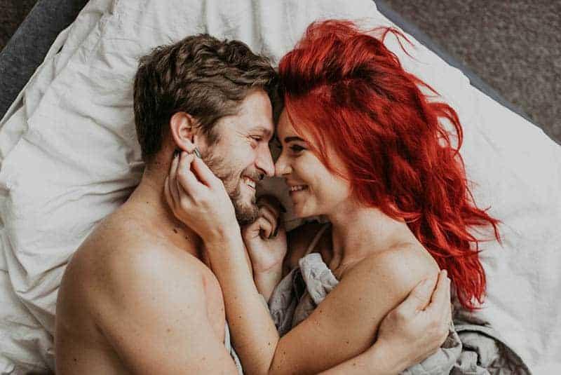 Frau mit roten Haaren, die Manngesicht berühren
