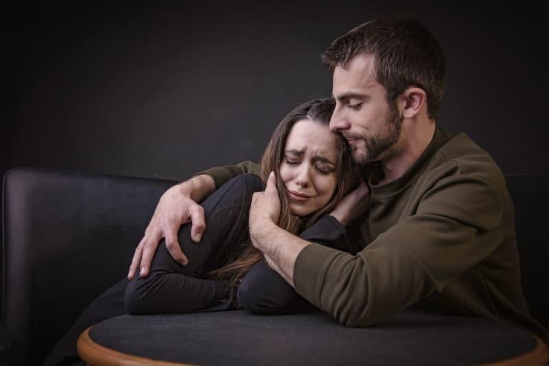 Junger Mann tröstet seine Freundin