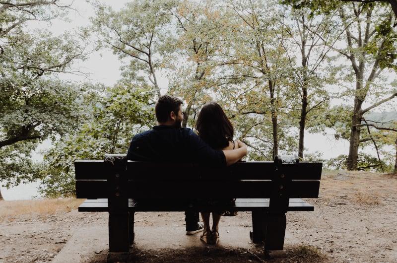 Mann, der zur Frau schaut, die auf schwarzer Holzbank vor hohen Bäumen während des Tages sitzt