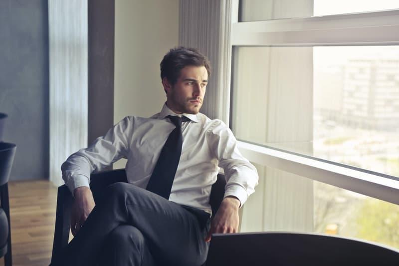 Mann in weißen Hemd sitzt