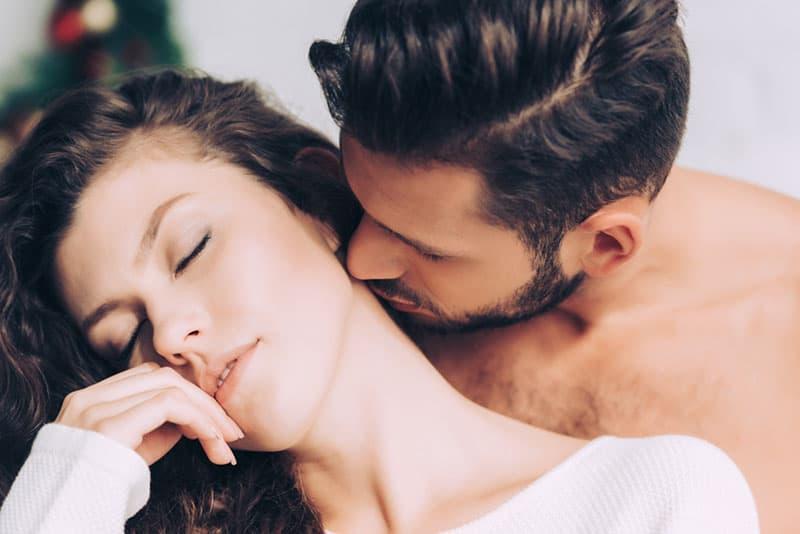 Mann küsst Frau Hals