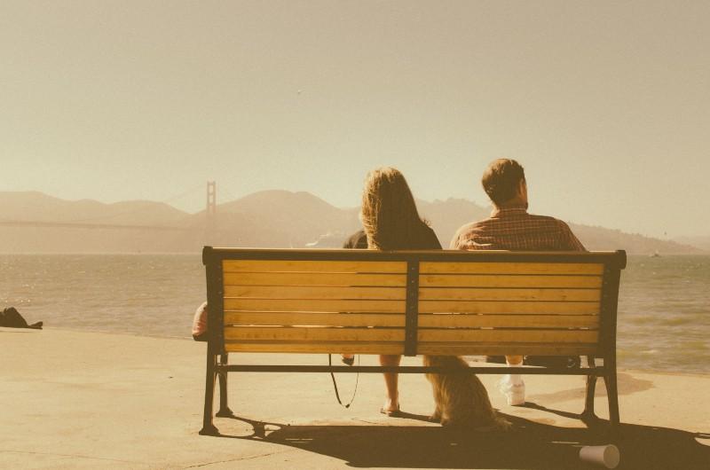 Mann und Frau sitzen auf der Bank neben dem Gewässer