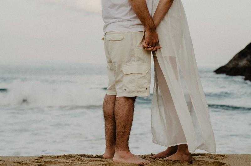 Mann und Frau stehen am Meer, während sie Hände halten