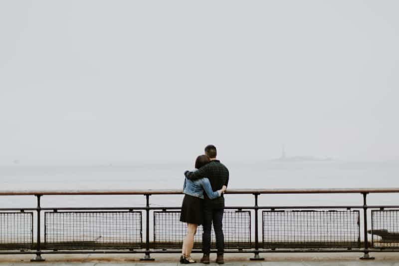 Paar, das vor Zaun nahe Gewässern steht (2)