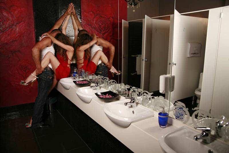 Paar küsst leidenschaftlich in der öffentlichen Toilette