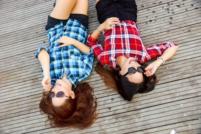 Zwei Mädchen mit Sonnenschirmen liegen auf dem Pier