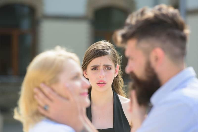 eifersüchtige Frau, die Mann und Frau auf der Straße ansieht