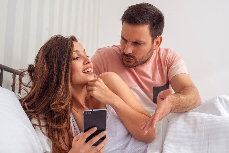 eifersüchtiger Mann, während Frau am Telefon SMS