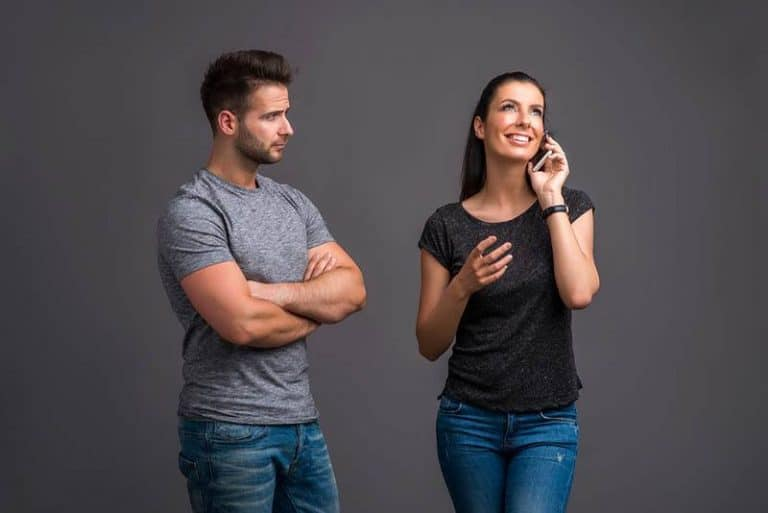 eifersüchtiger Mann, während Frau am Telefon spricht