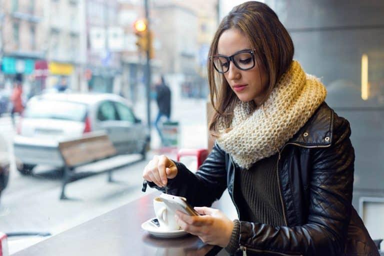ein Mädchen, das alleine beim Kaffee und einem Schlüssel auf ihrem Handy sitzt