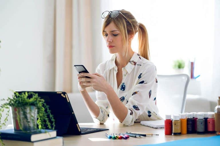 ein Mädchen sitzt im Büro und einen Schlüssel auf ihrem Handy