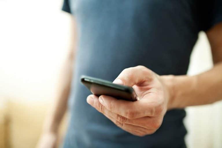 ein Mann, der ein Handy in den Händen hält