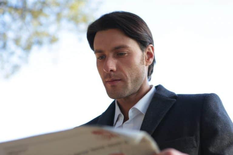 ein Mann mit einer Zeitung in den Händen