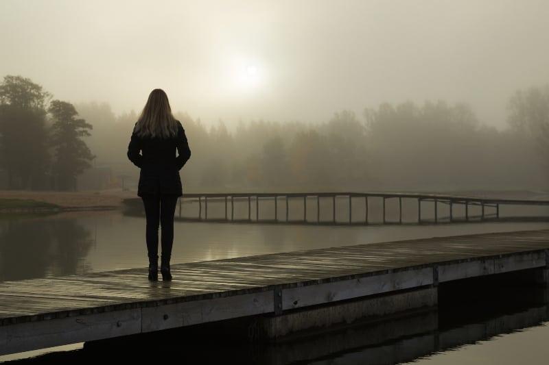 eine junge Frau allein am See