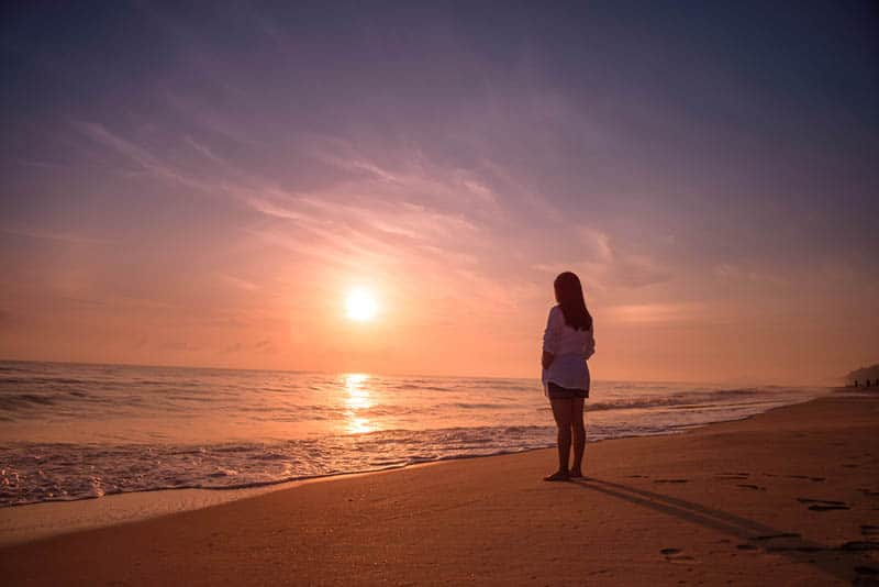 einsame Frau, die am Strand steht